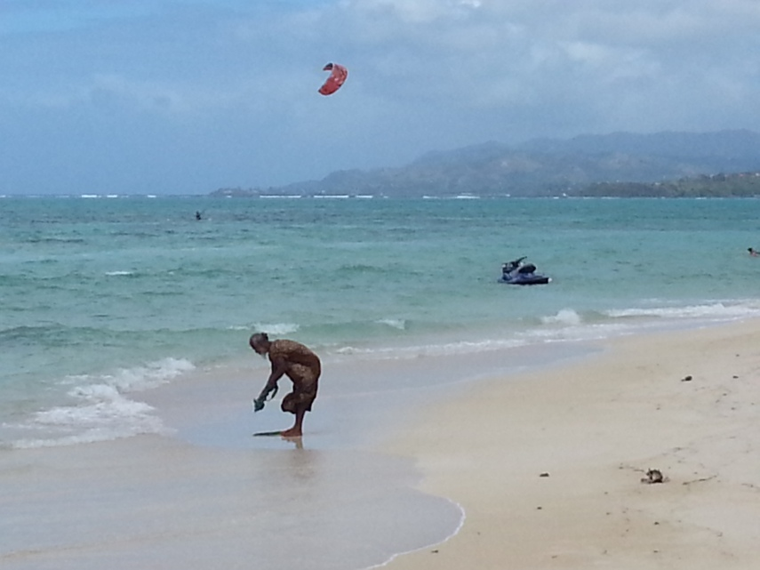 This chap is doing his laundry as kite surfers enjoy the wind blast
